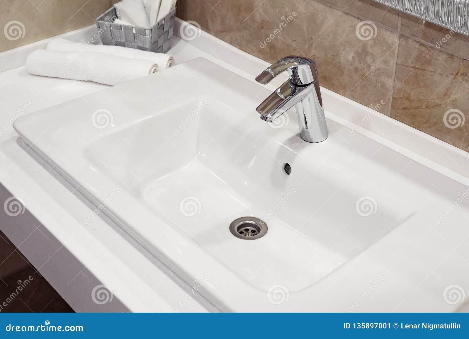 Toalhas brancas empilhadas dos termas no banheiro moderno