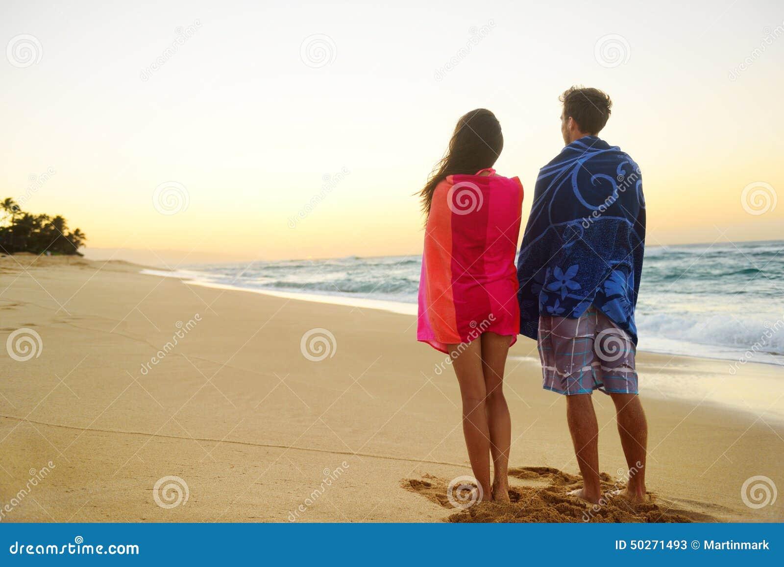 Toalhas novas dos pares sobre ombros na areia da praia