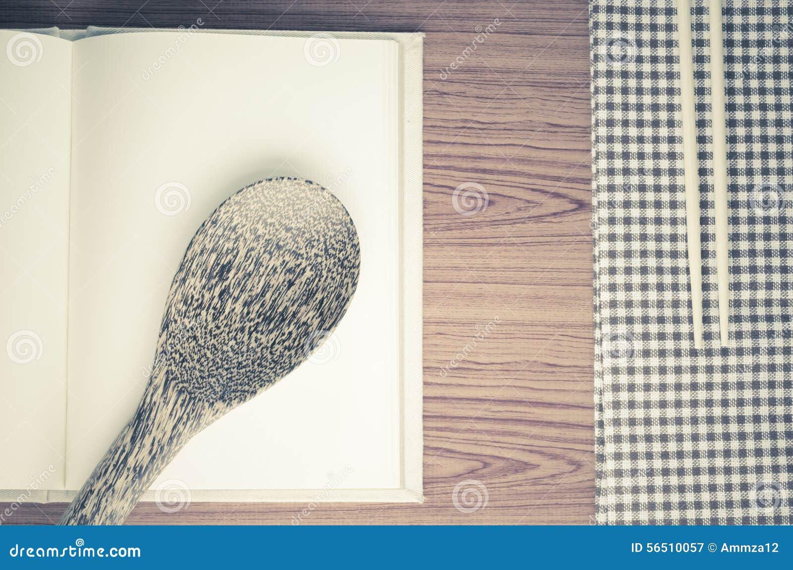 Toalla de cocina con la cuchara en el fondo de madera