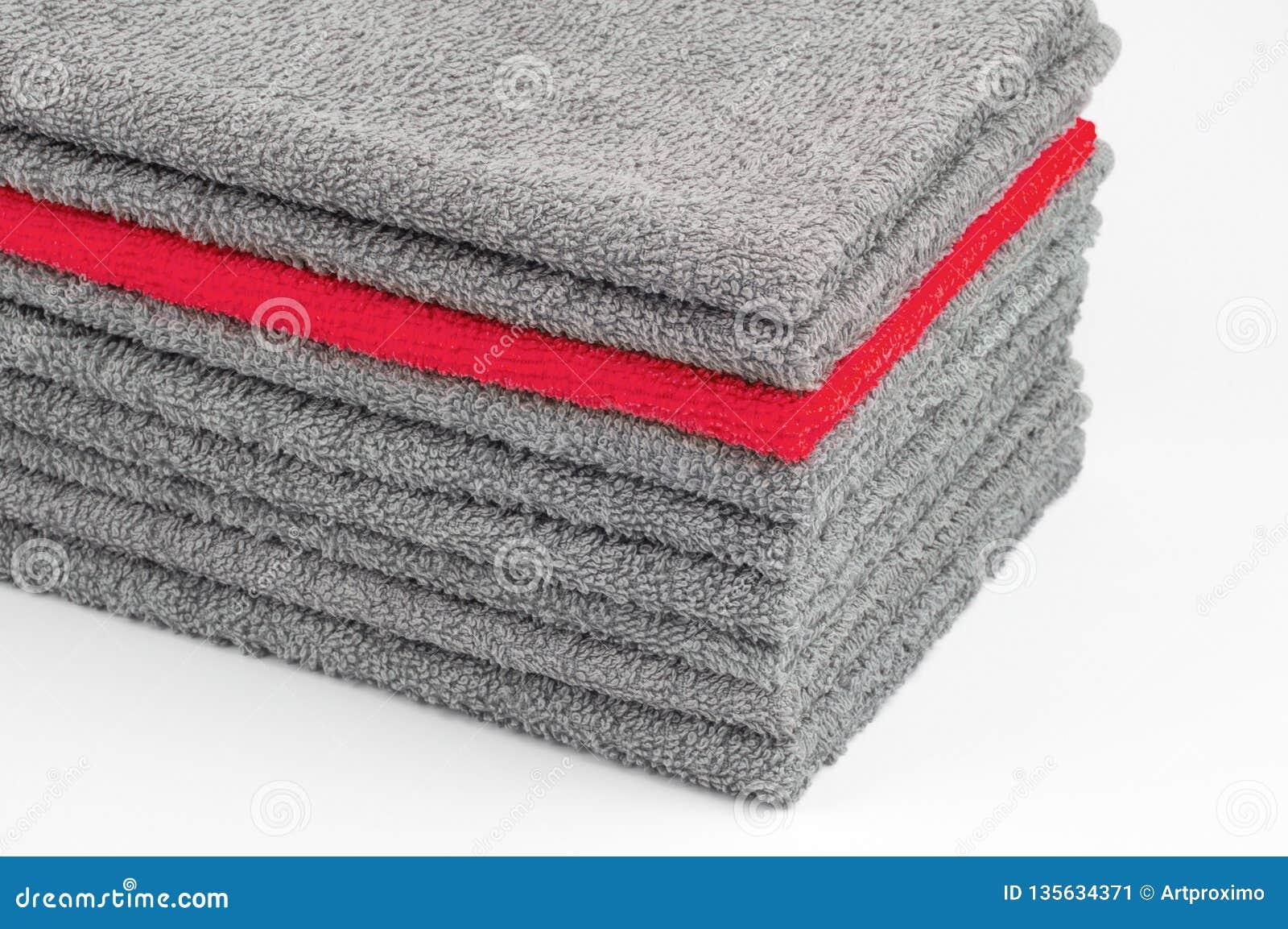 Toalla de Terry roja brillante en la pila otras grises Fondo blanco contraste conceptual del color
