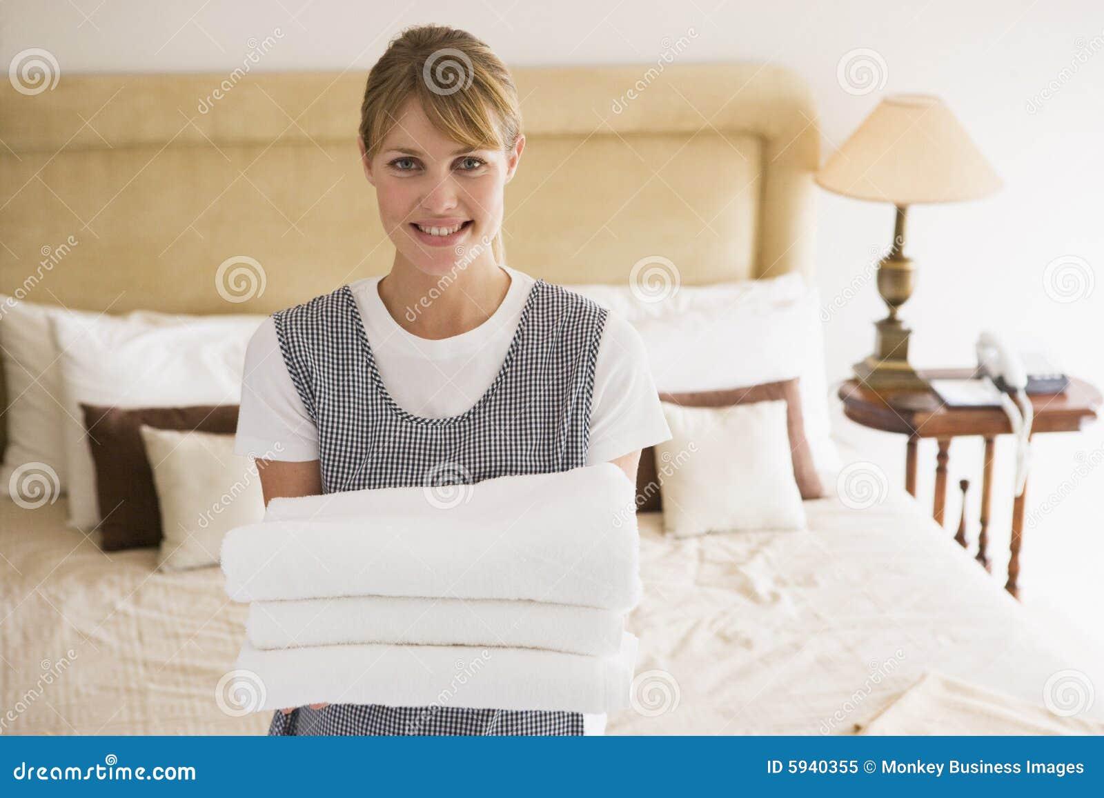 Toallas de la explotación agrícola de la criada en la sonrisa de la habitación