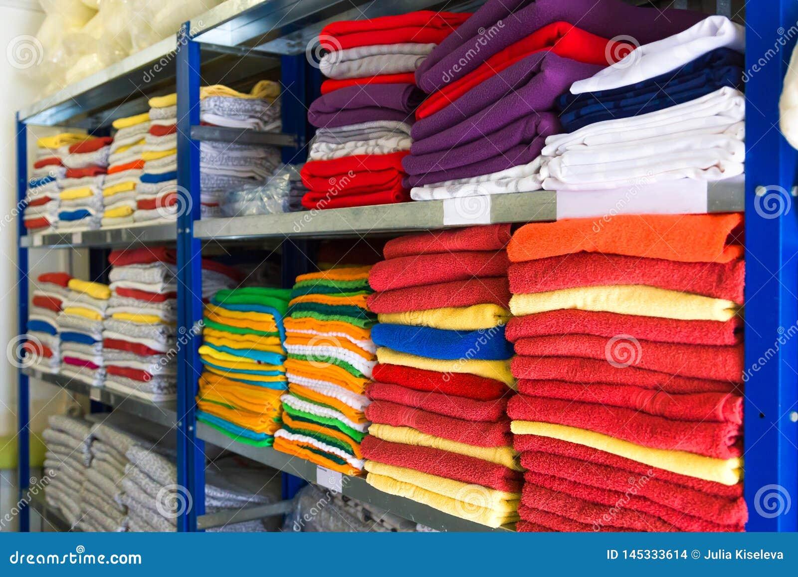 Toallas, sábanas y ropa en el estante