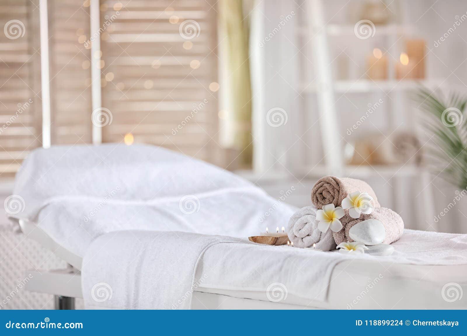 Toallas y velas en la tabla del masaje en salón del balneario Lugar para la relajación