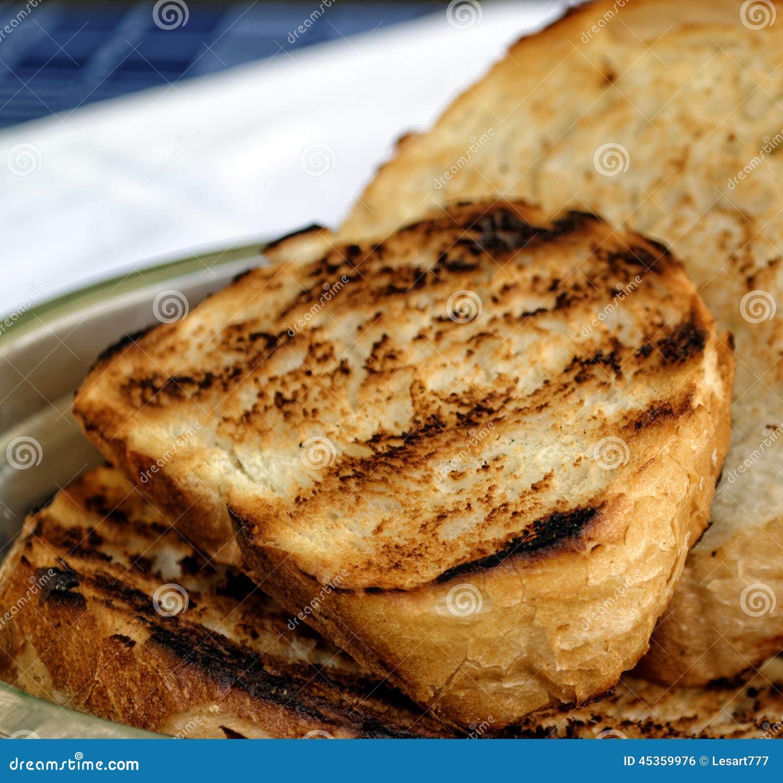 Toasted a coupé en tranches le pain blanc dans la cuvette en métal