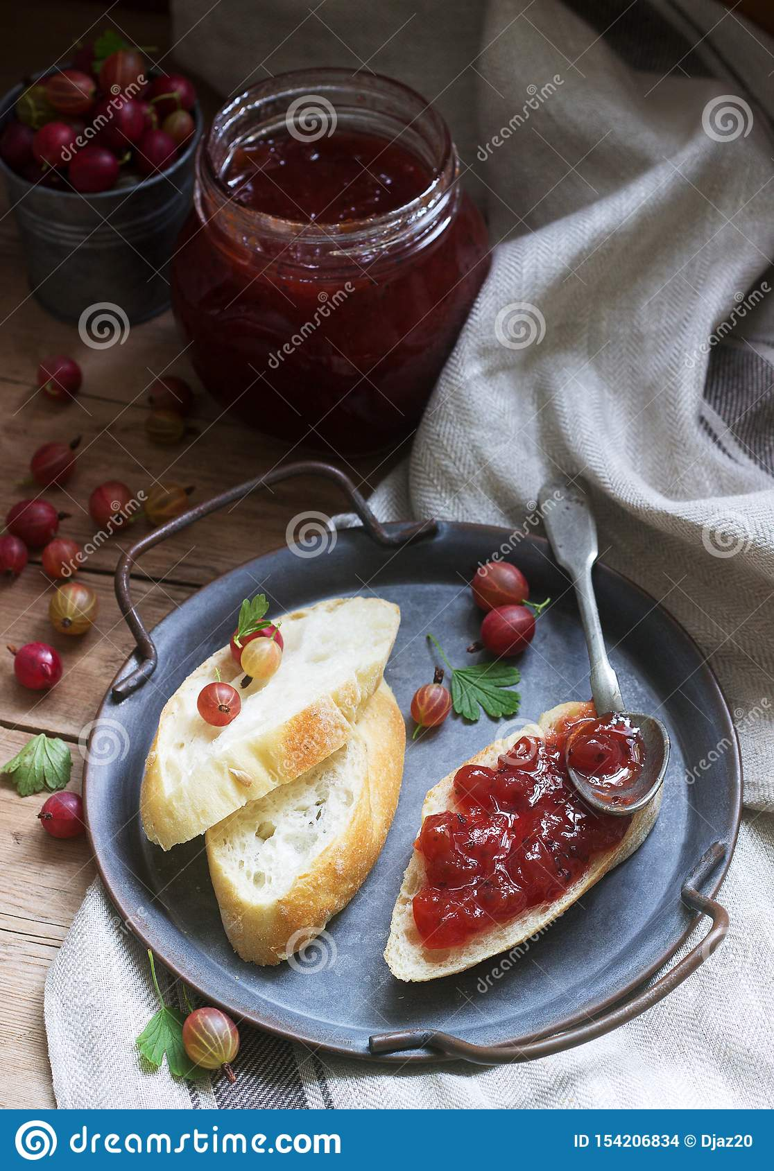 Toasts with gooseberry jam and gooseberries on a tin tray. Rustic style