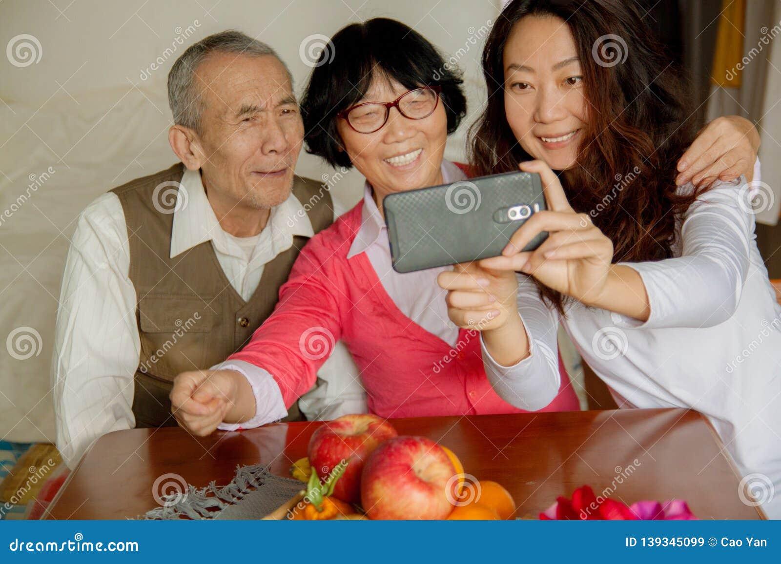 Tochter und ältere Eltern unter Verwendung des Smartphone zu Hause
