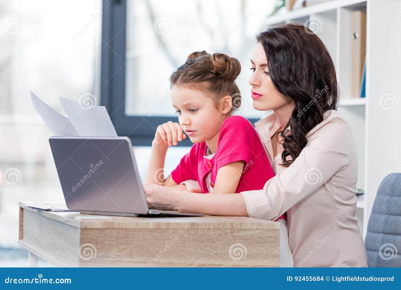Tochter und Mutter, die mit Laptop arbeiten und Papiere im Büro betrachten