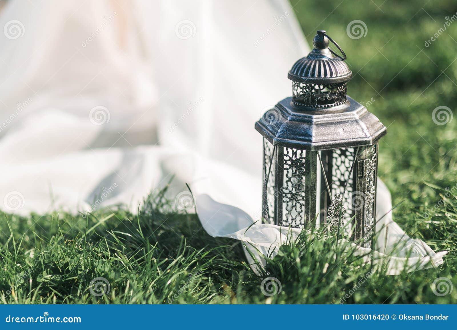 Todavía casarse la linterna negra de la vida en hierba y el tule blanco en estilo rústico
