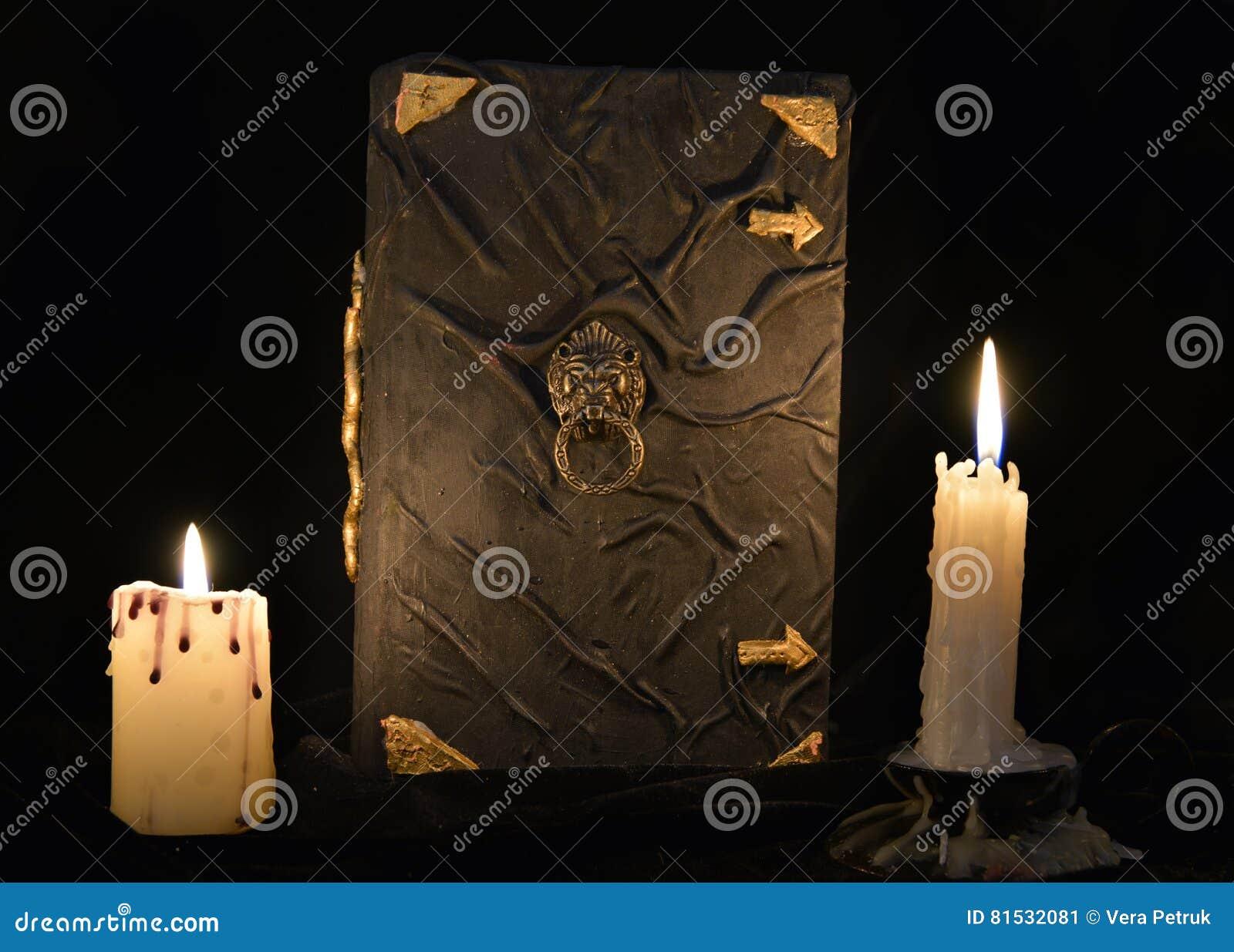 Todavía del místico vida con el libro de la magia negra y dos velas ardientes