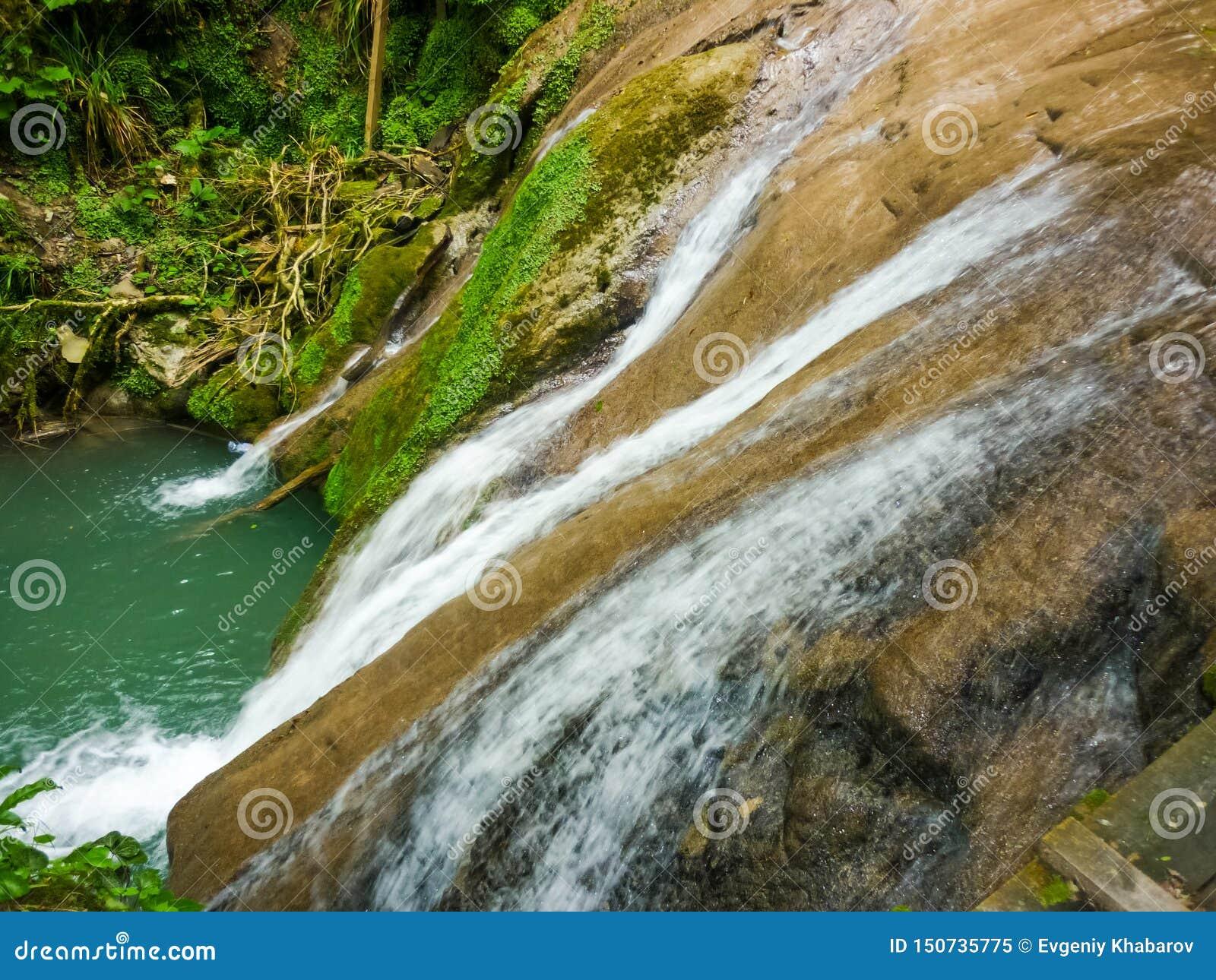 Todavía hermoso, incluso con flujo reducido en la caída temprana, se derrama a través y conecta en cascada sobre un acantilado cu