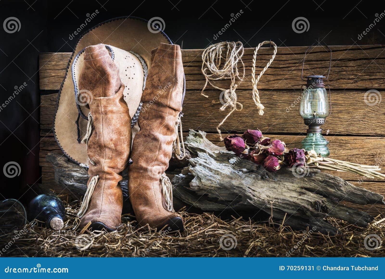 Todavía la fotografía de la vida con marrón del oeste americano del rodeo  sentía el sombrero de vaquero y las botas de cuero tradicionales en fondo  del ... e0eef8e4062