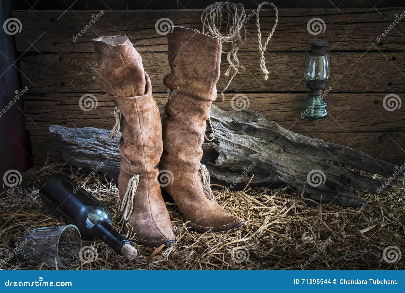 Todavía fotografía de la vida con las botas de cuero tradicionales en fondo  del granero del rancho del vintage bc2344a7229