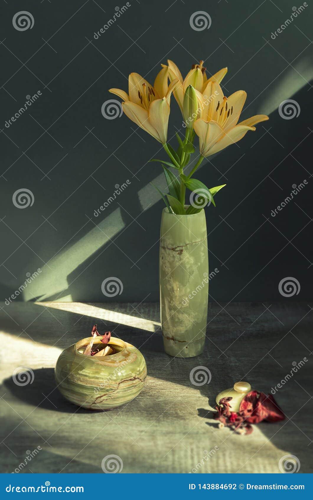 Todavía vida con los lirios en un florero verde hecho de piedra natural