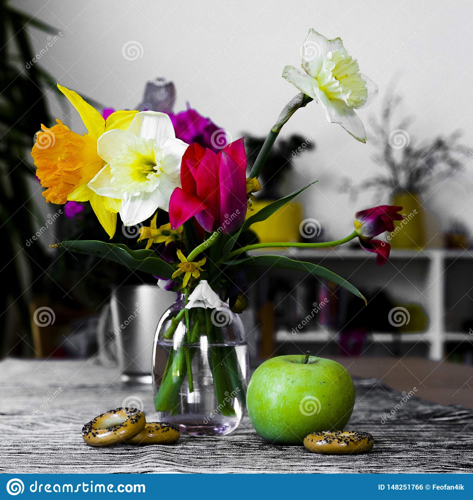 Todavía vida de flores en un florero, la composición de tulipanes y de narcisos con Apple y el secado en el fondo