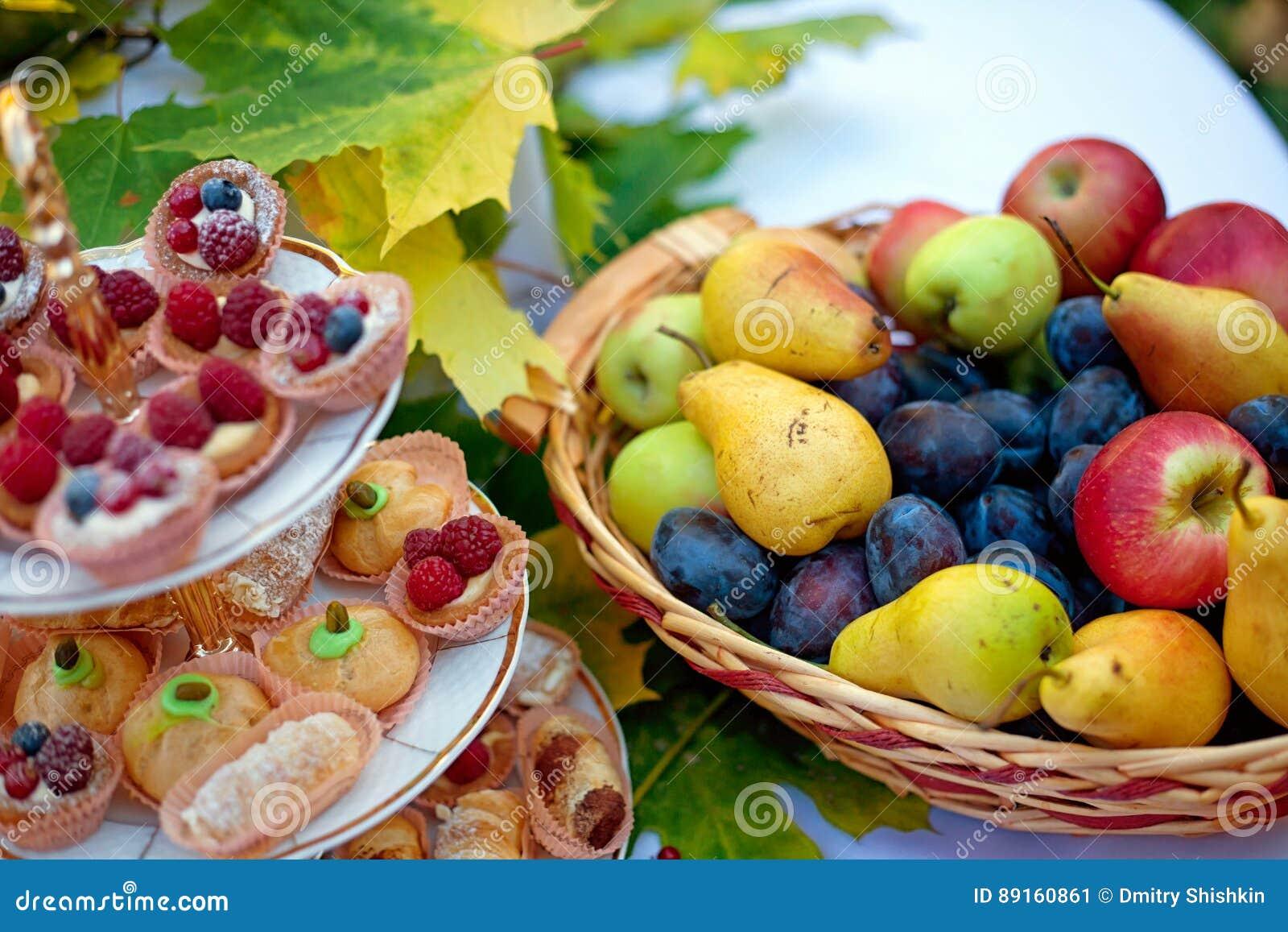 Todavía vida de la fruta fresca en la cesta y de la torta en una placa con las hojas de otoño