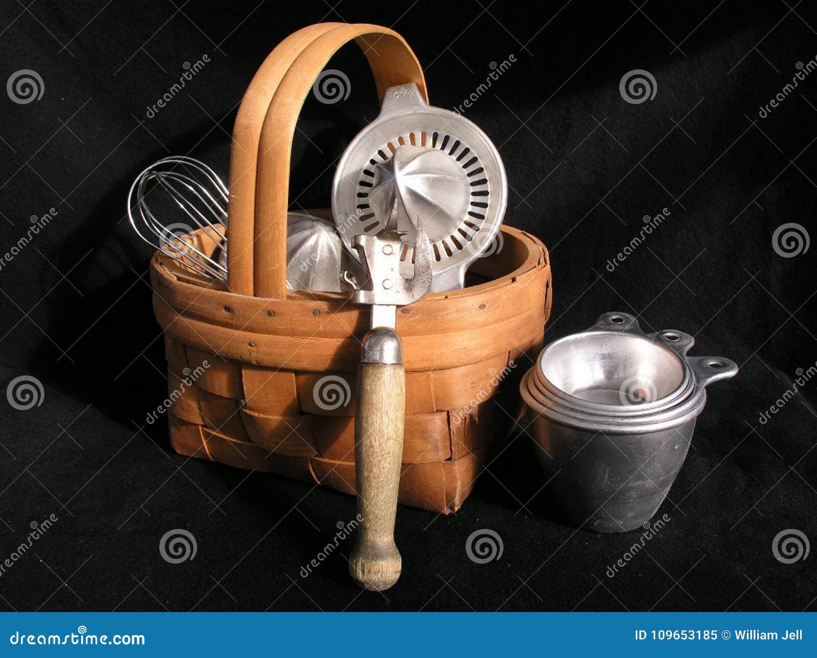 Todavía vida de los utensilios retros de la cocina en cesta de mimbre