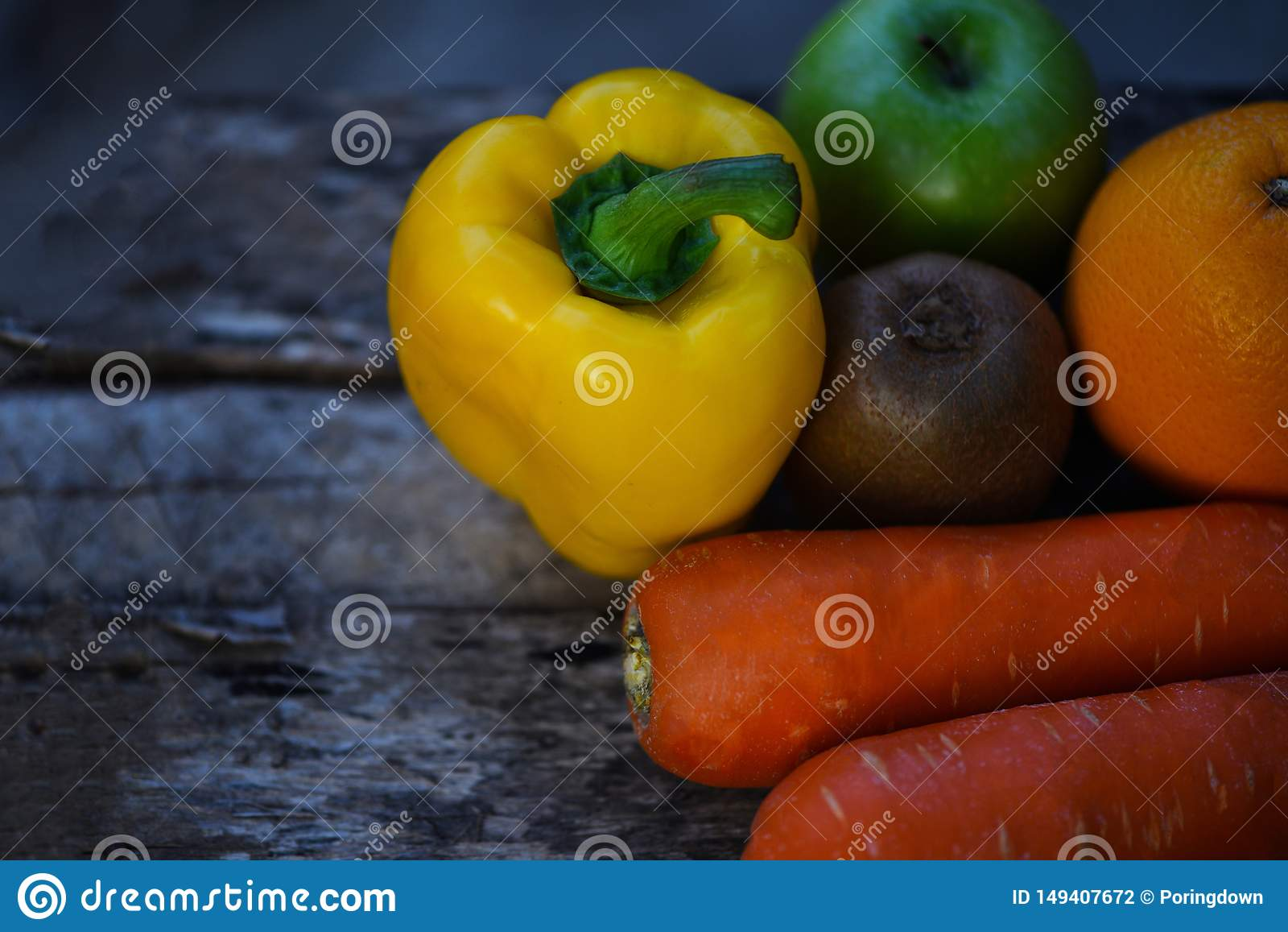 Todav?a fruta de la vida con la naranja amarilla y el kiwi de la zanahoria de la manzana del verde del paprika en la madera r?sti
