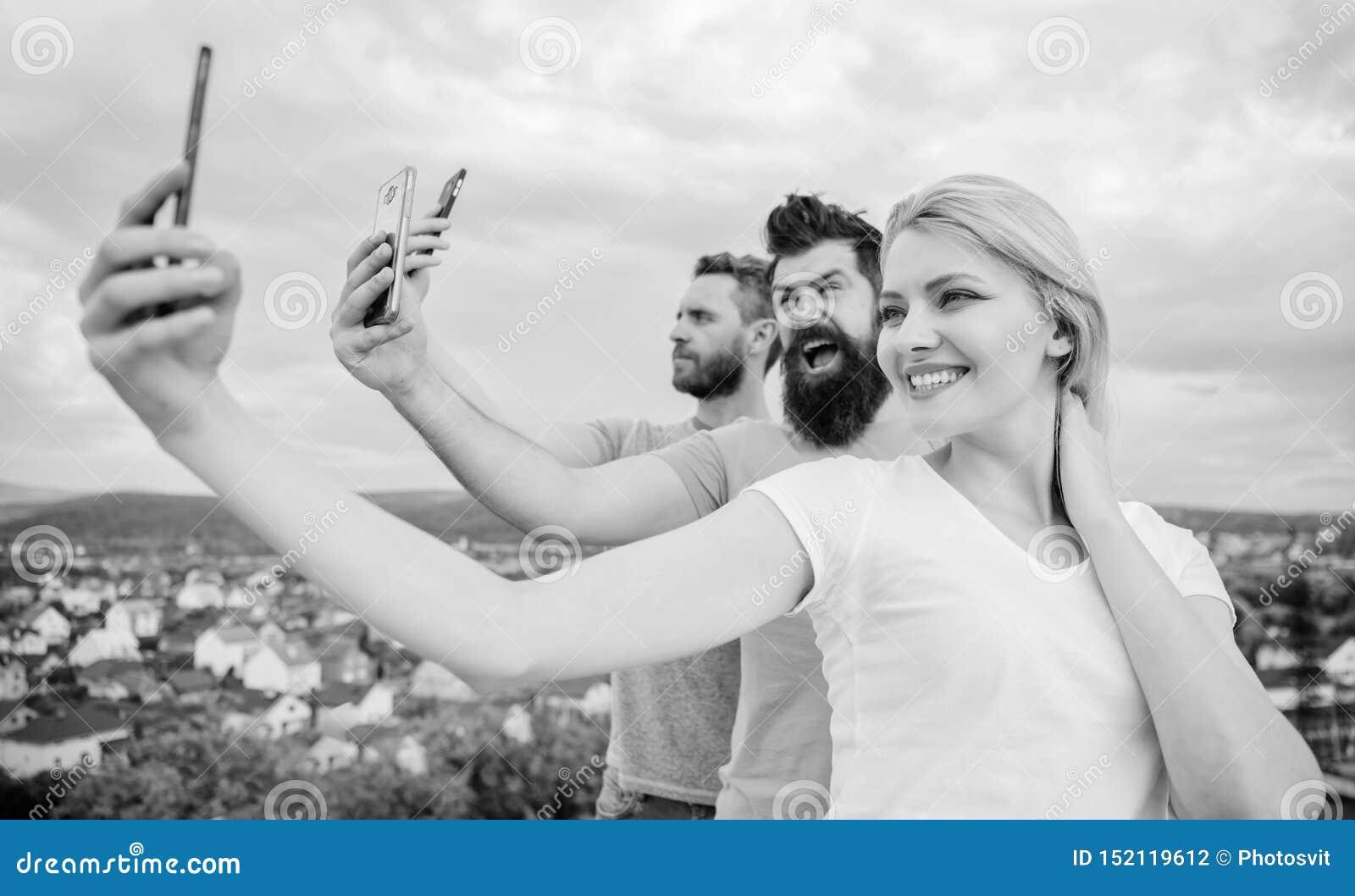 Todays selfie. Pretty woman and men holding smartphones in hands. People enjoy selfie shooting on natural landscape