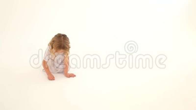 Toddler Baby Child Girl Rosy Cheeks Blond Curly Hair White Dress Sitting Drawing Heart Fingers On Floor Background Stock Video