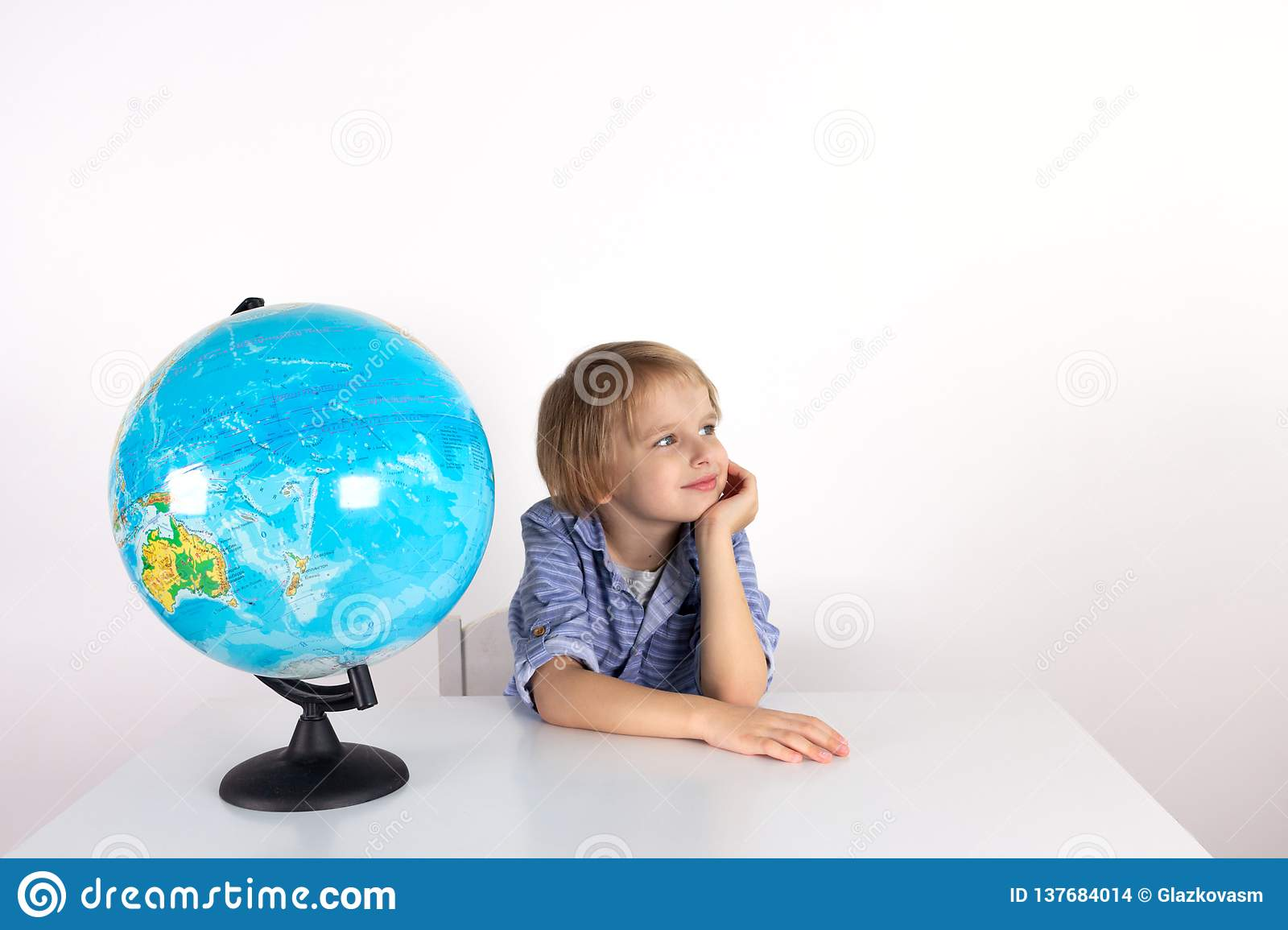 Toddler boy with a globe on the lesson of practical life on a white background, Montessori class, isolate.