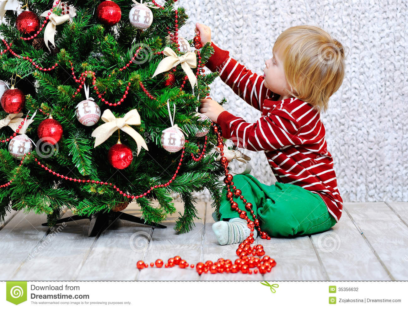 Toddler decorating christmas tree stock photography for X mas decorations for kids