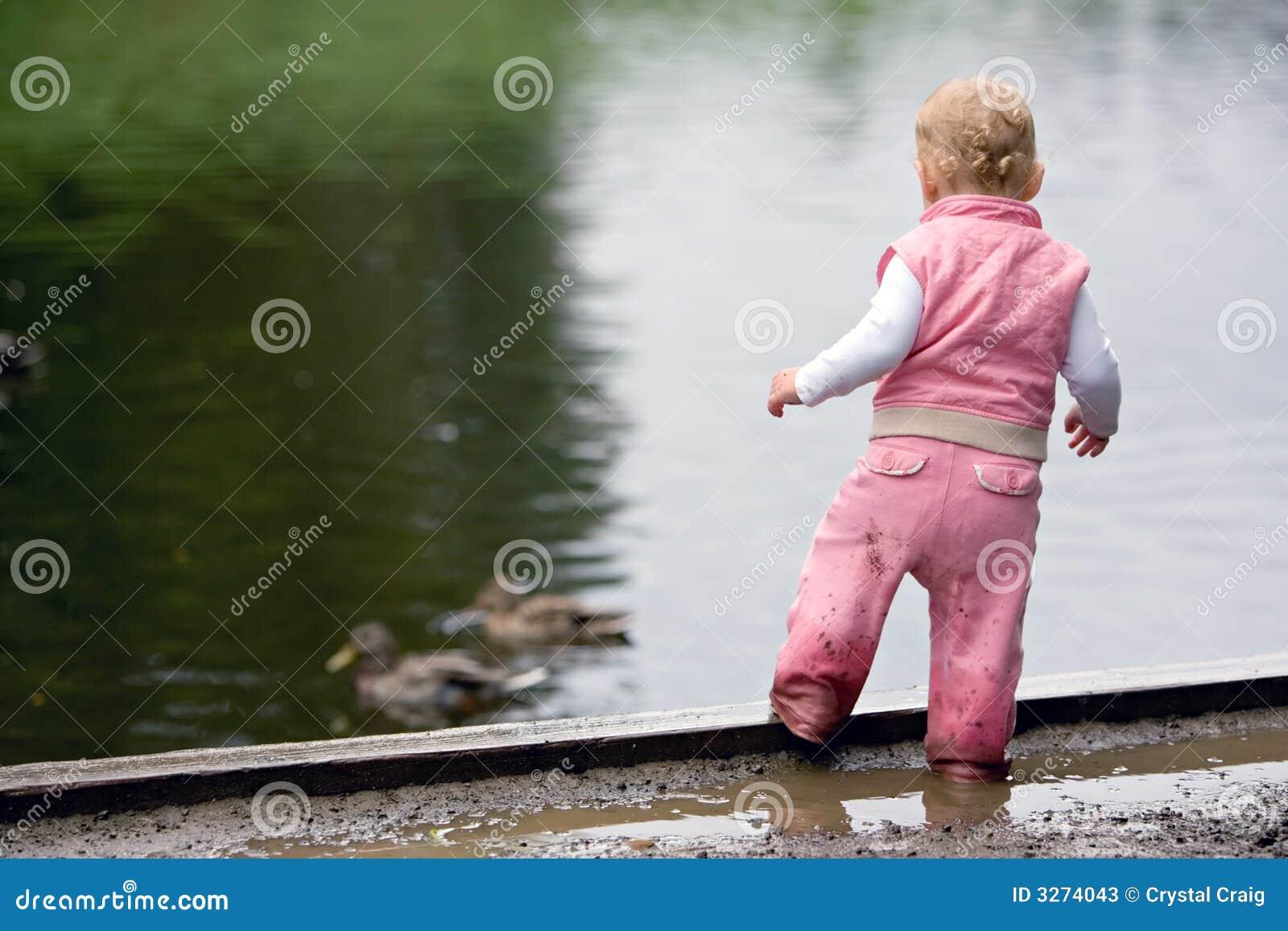 Toddler beside duck pond