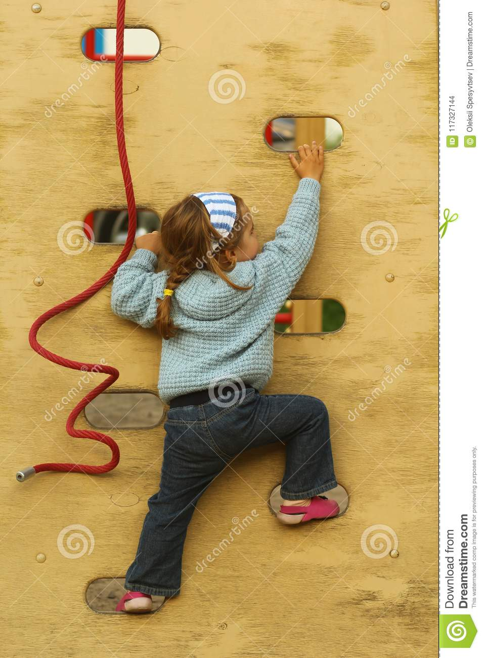 Toddler Girl In Bandana And Hand Made Knitted Cardigan Climbing The Wall On The Playground