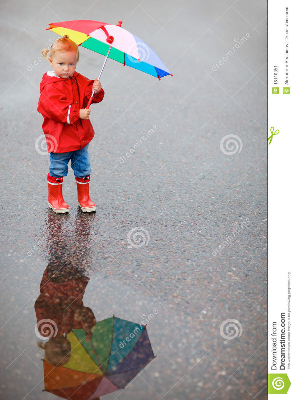 toddler girl with colorful umbrella on rainy day stock