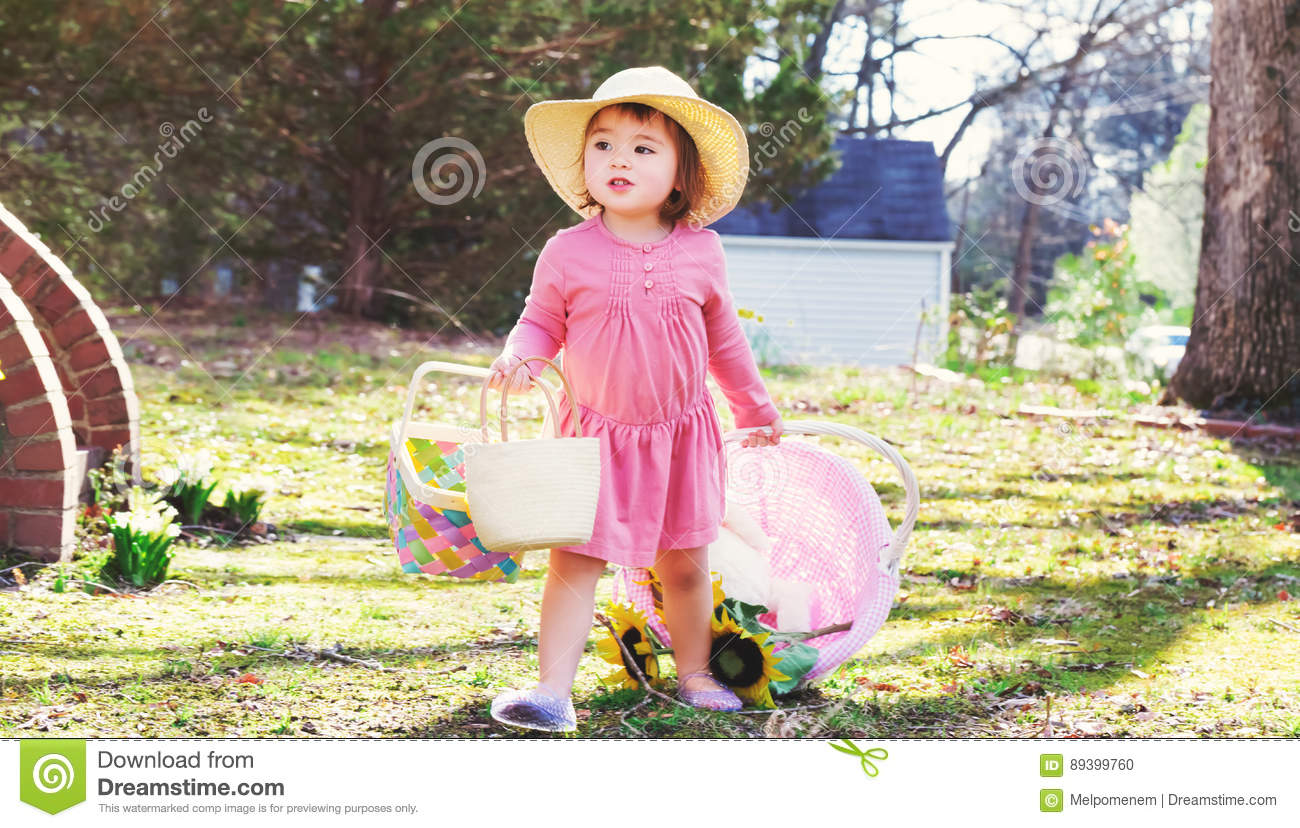 Toddler Girl Playing Outside With An Easter Basket Stock Photo