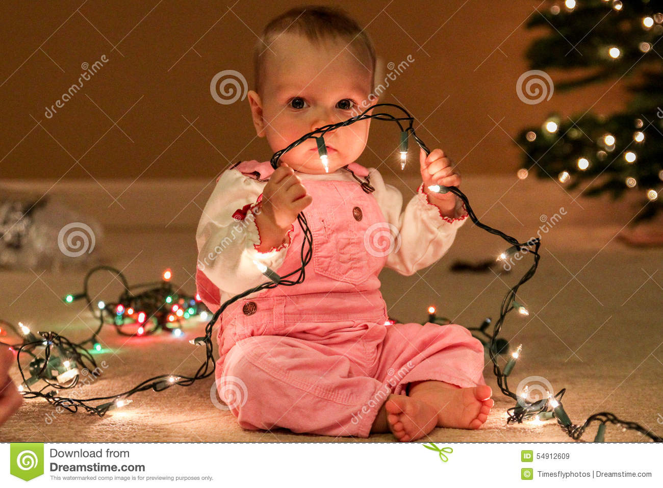 Toddler Girl With String Of Christmas Lights Stock Photo