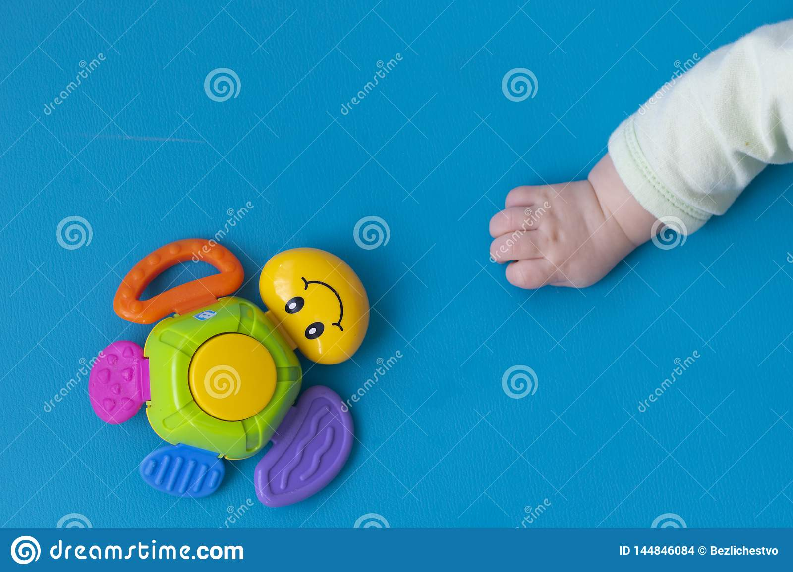 The Toddler New Born hand stretches to the right to the toy of a multi-colored turtle with a smile on a blue background. Close-