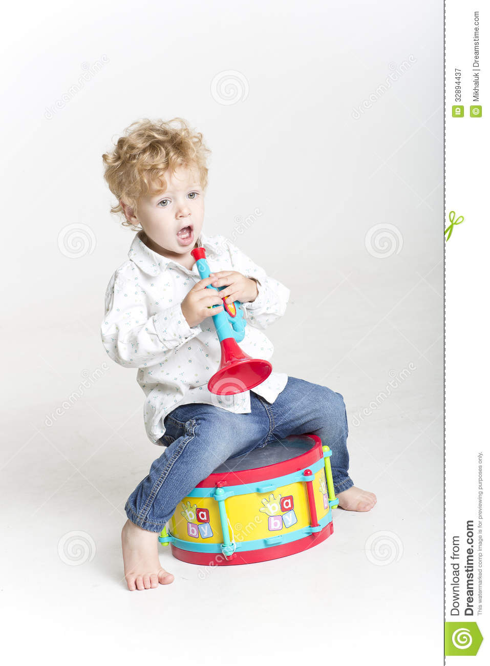 Musical Toys For Toddlers Boys : Toddler is playing with toy musical instruments on white