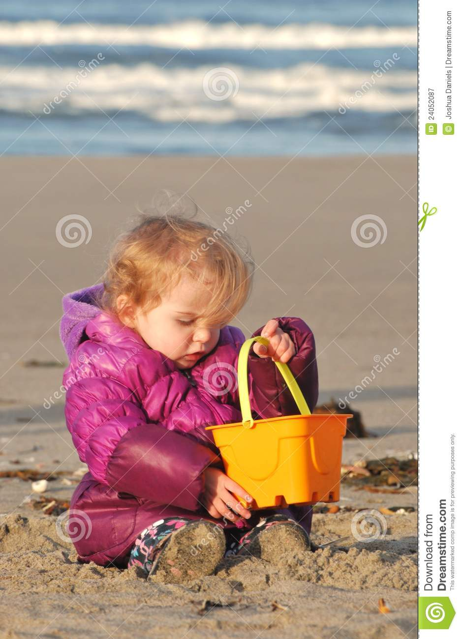 A toddler plays with a sand pail at the beach