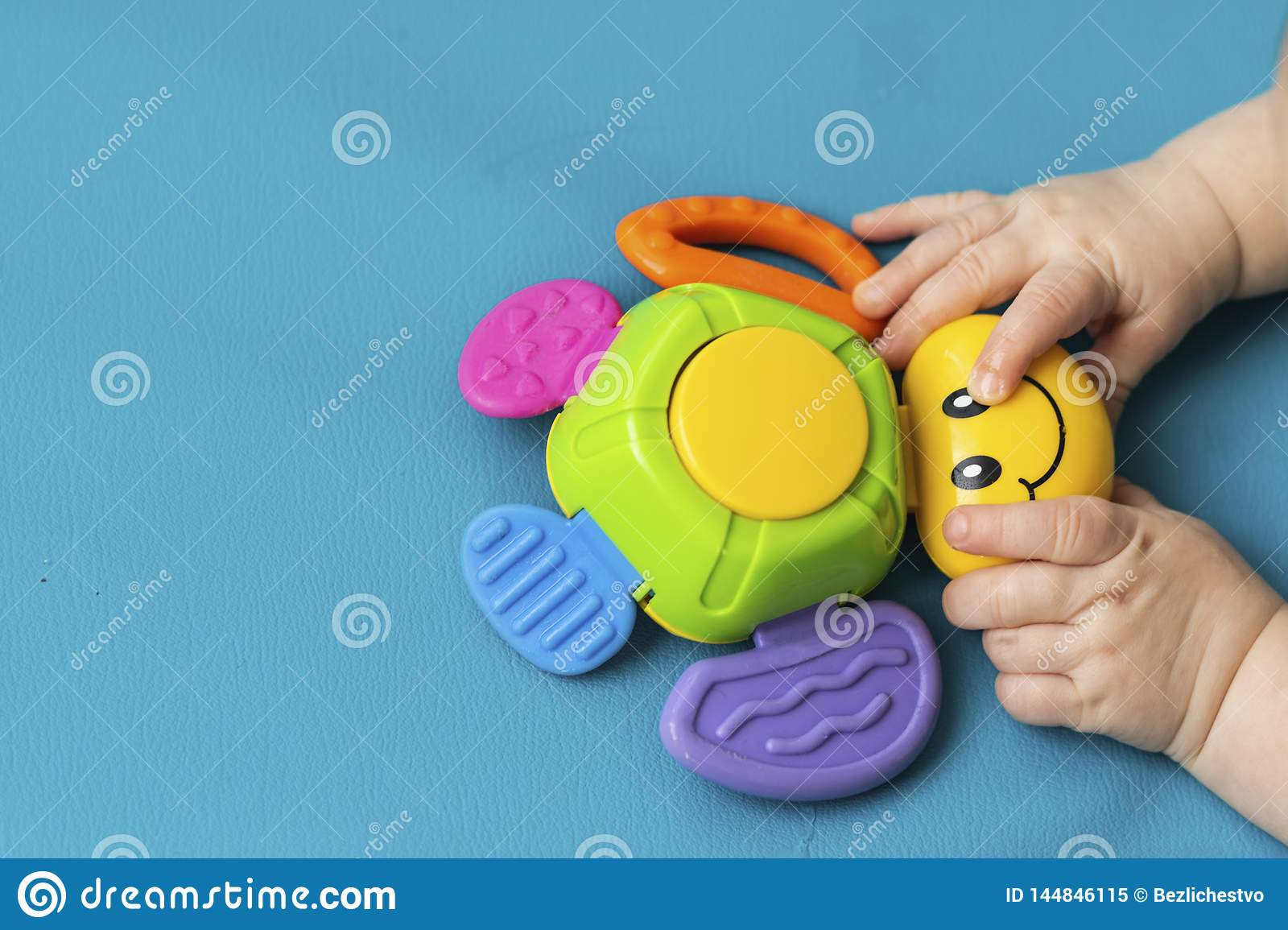 Toddler`s little hands new born hold a toy bug with a smile on a blue background. Aquamarine. Close-up. Copy Spase