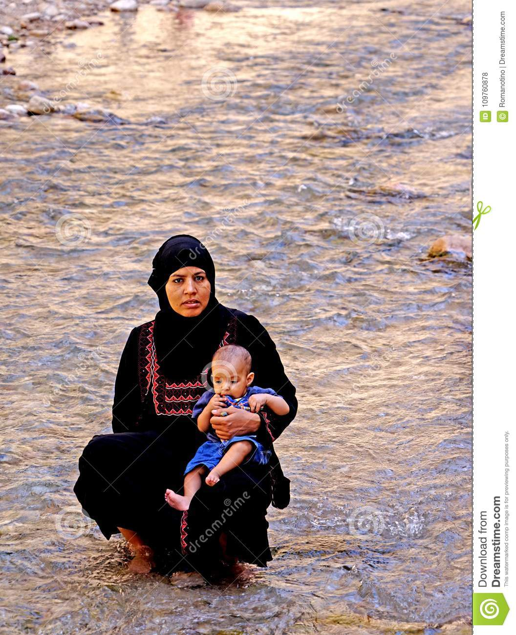 Woman with her baby in the river of The Todra gorges in Morocco