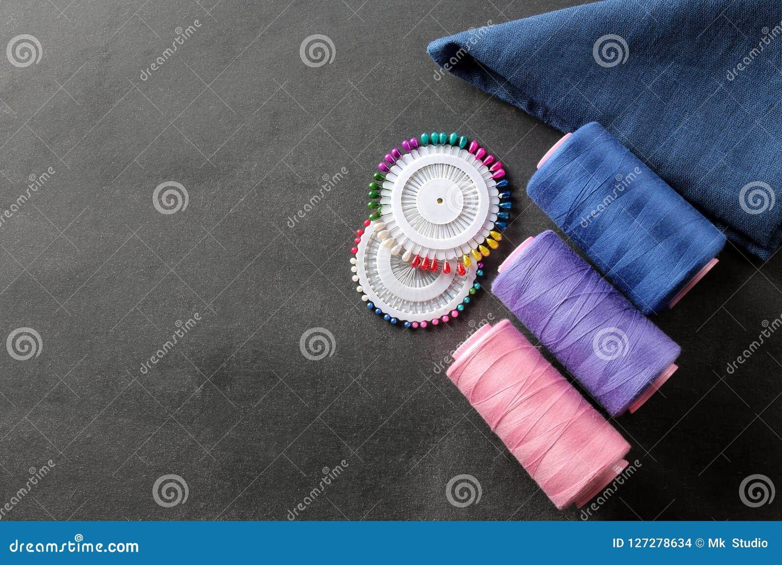 Toebehoren voor het naaien van een spoel met draad, spelden en een stuk van doek op een zwarte achtergrond met een plaats voor ee