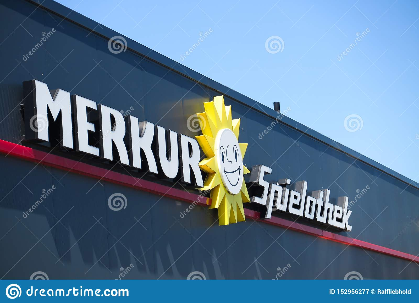 TOENISVORST, GERMANY - JUIN 28. 2019: Close up of text and sun logo on black facade with blue sky of Merkur Spielothek german