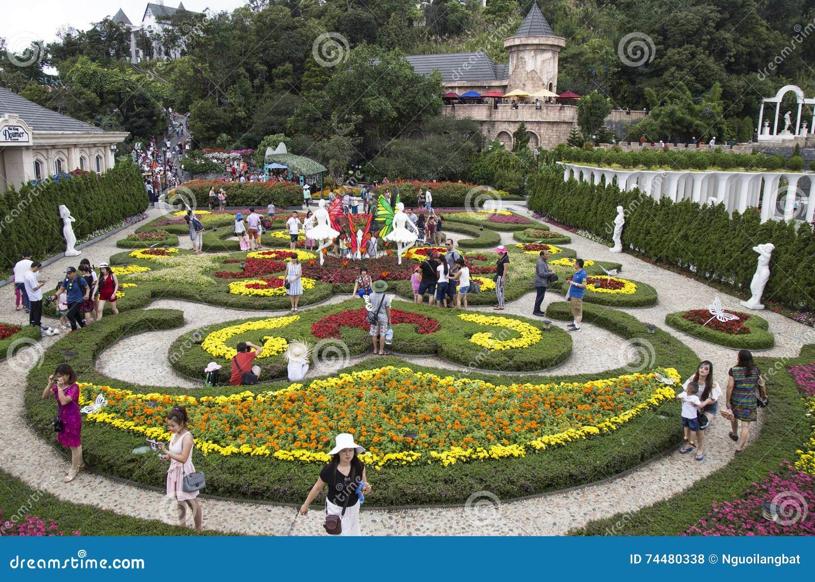 Bloem En Tuin : Toerist die een bloementuin met veel soort kleurrijke bloem in de