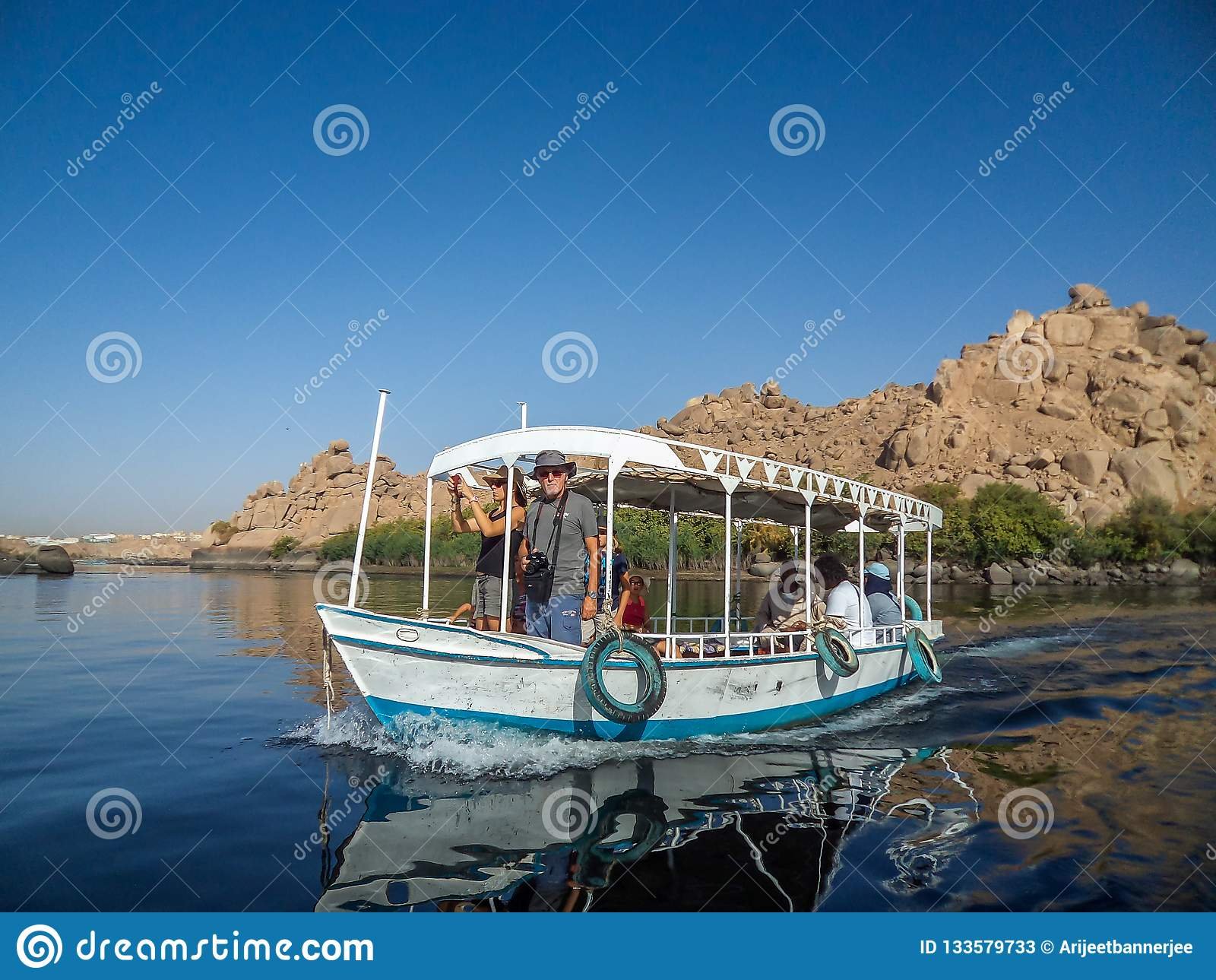 Toerist die van een rit op een kleine boot genieten die de rivier Nijl kruisen dichtbij Aswan, Egypte