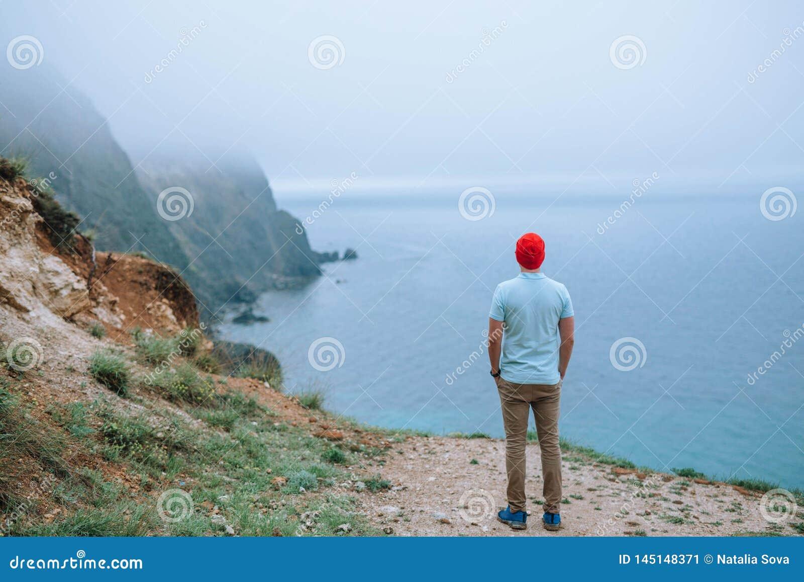 Toerist in een rode GLB-tribunes op een klip die het overzees overzien