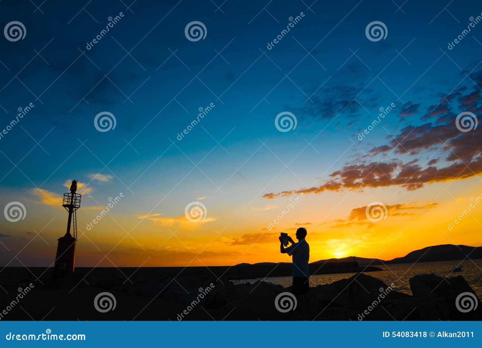 Toerist en vuurtoren bij zonsondergang