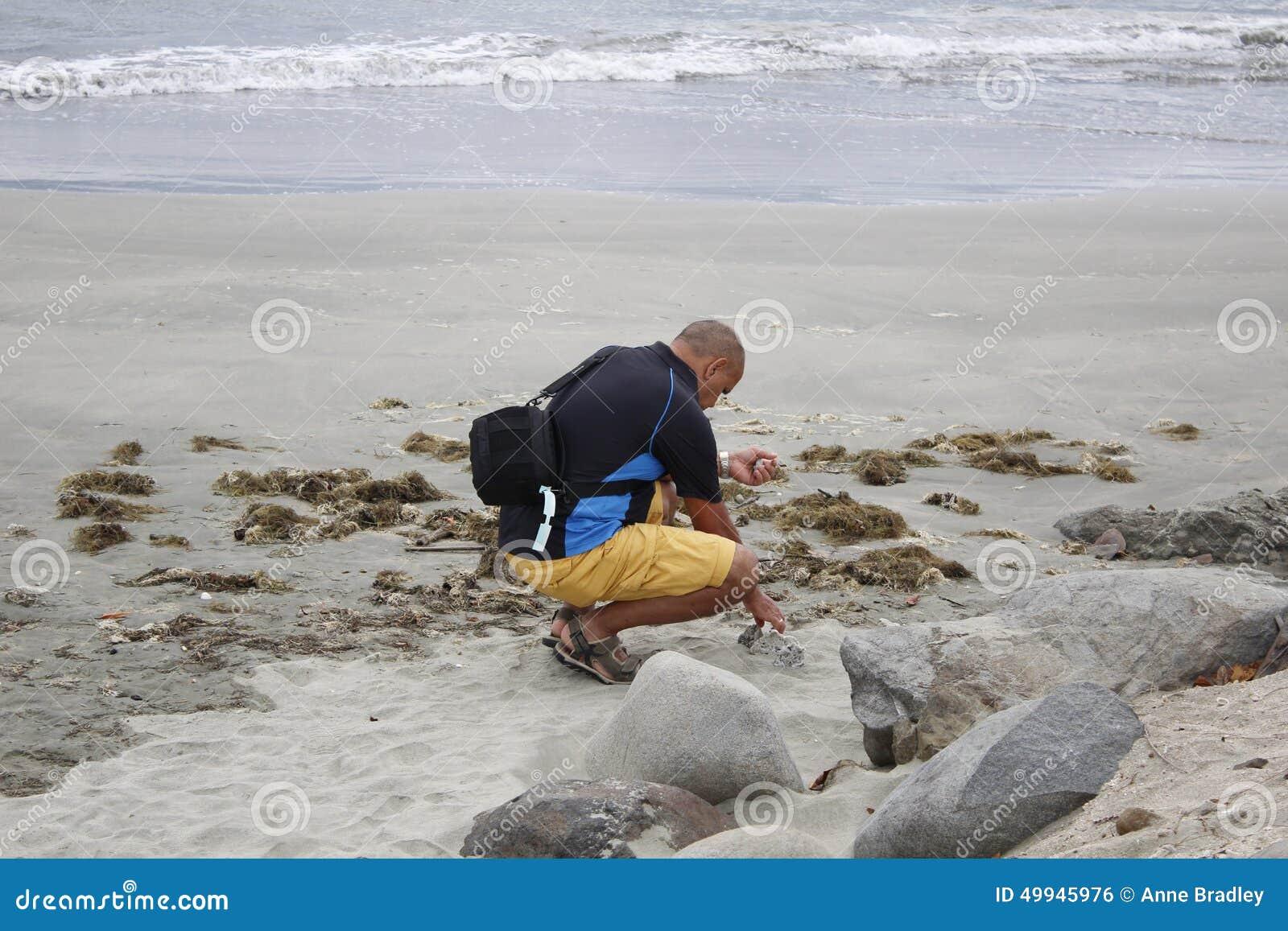Toerist het beachcombing bij schemer