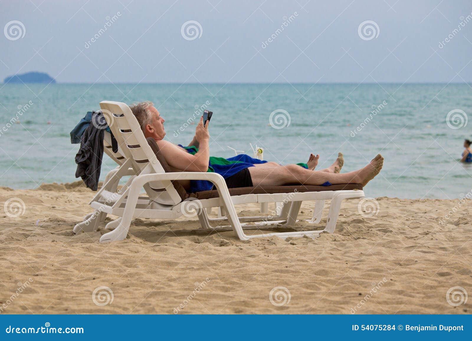 Toerist het ontspannen op a sunbed beack