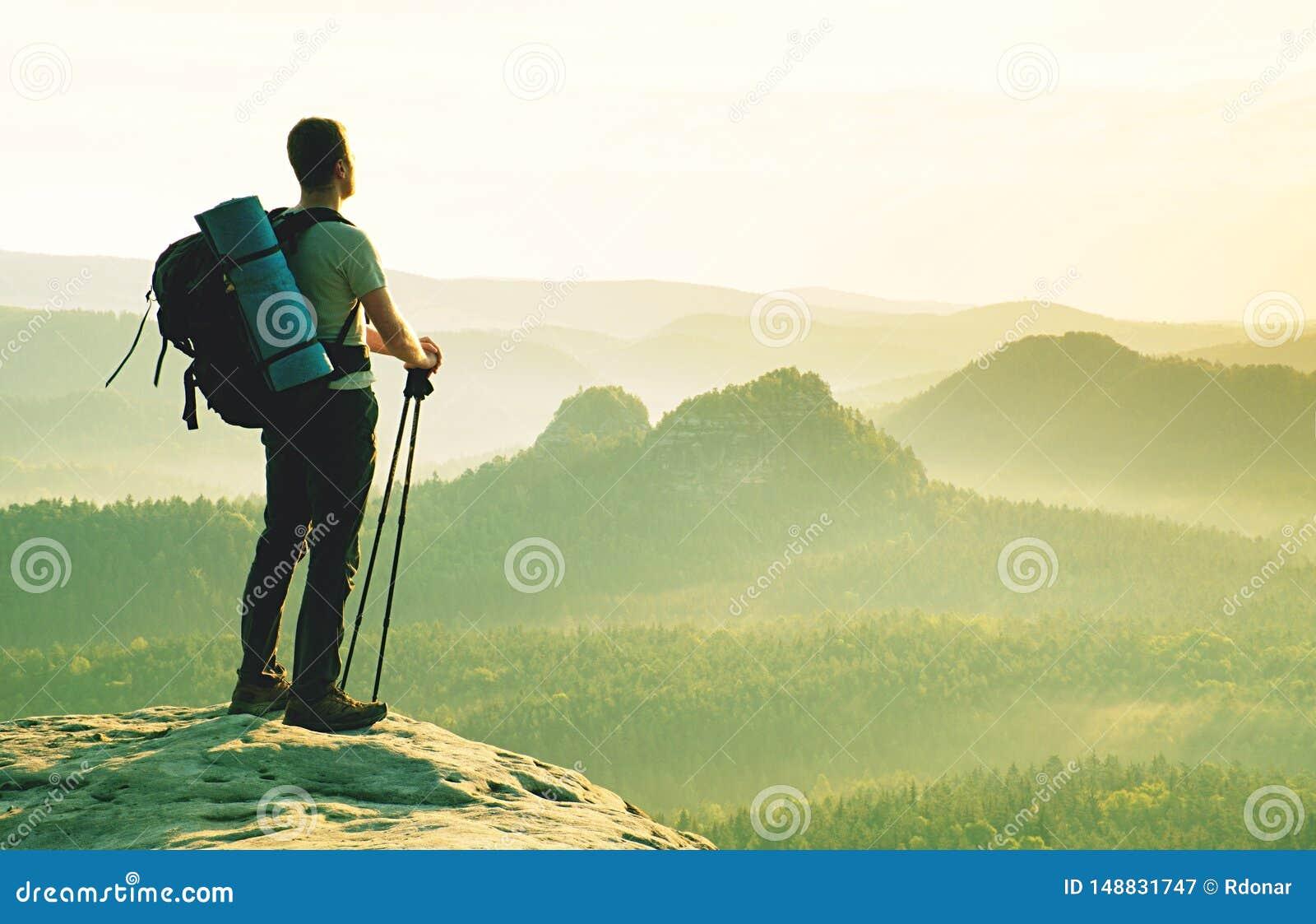 Toerist met in hand polen De zonnige rotsachtige top van het de lentelandschap
