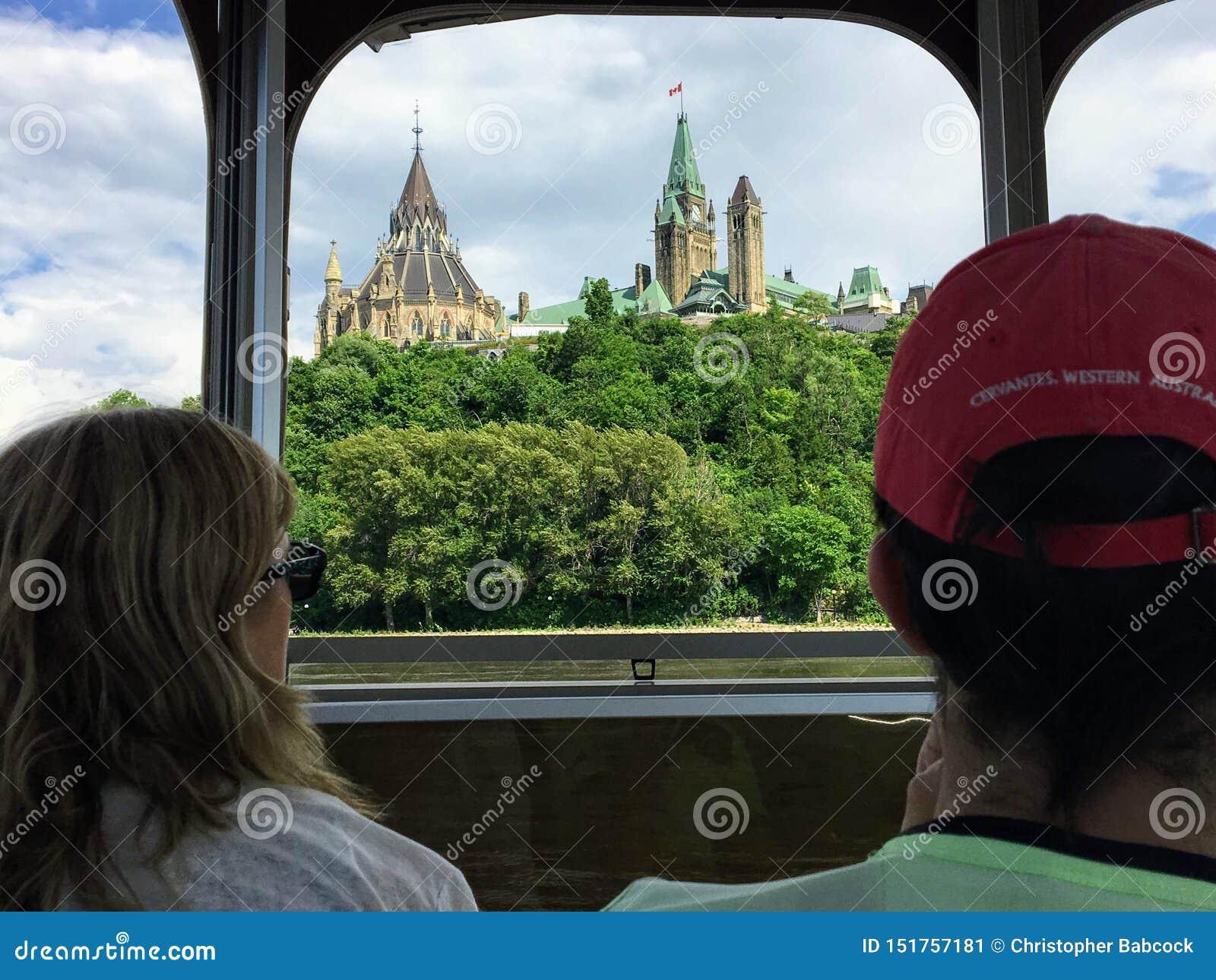 Toeristen die in de meningen van het Parlement Heuvel en cityscape nemen terwijl het nemen van een reisboot over de Rivier van Ot
