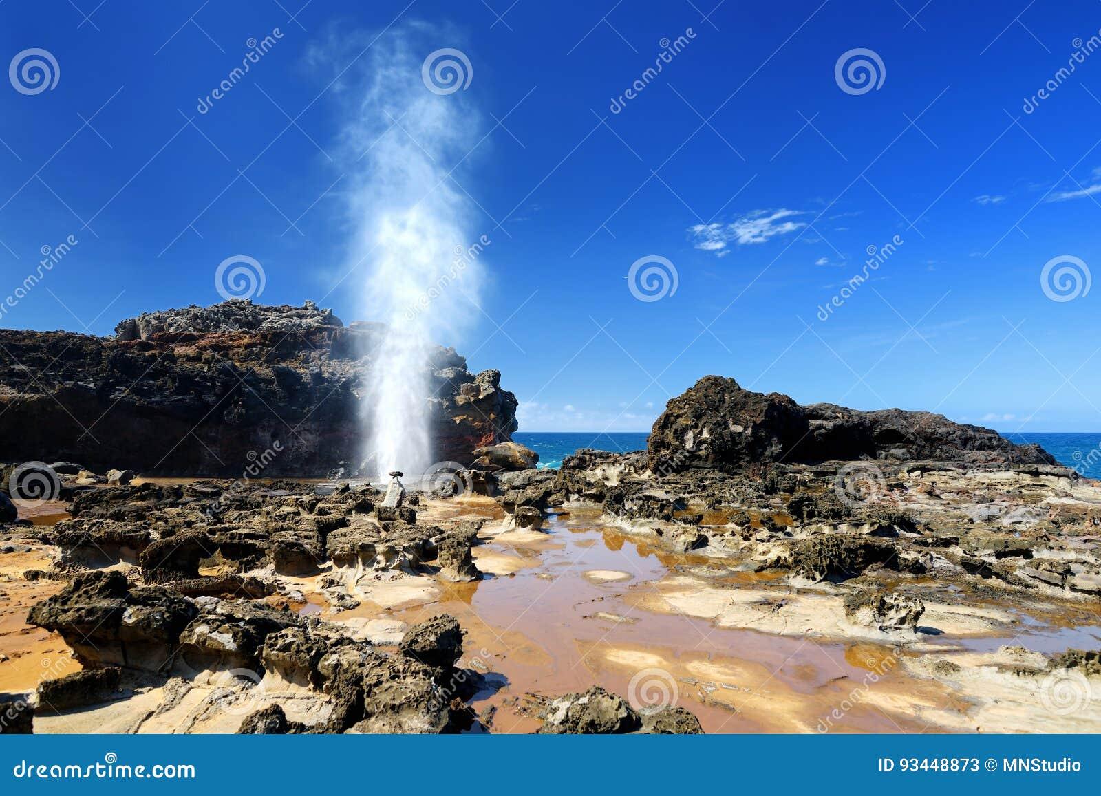 Toeristen die de Nakalele-gietgal op de kustlijn van Maui bewonderen Een straal van water en lucht wordt hevig binnen gedwongen u