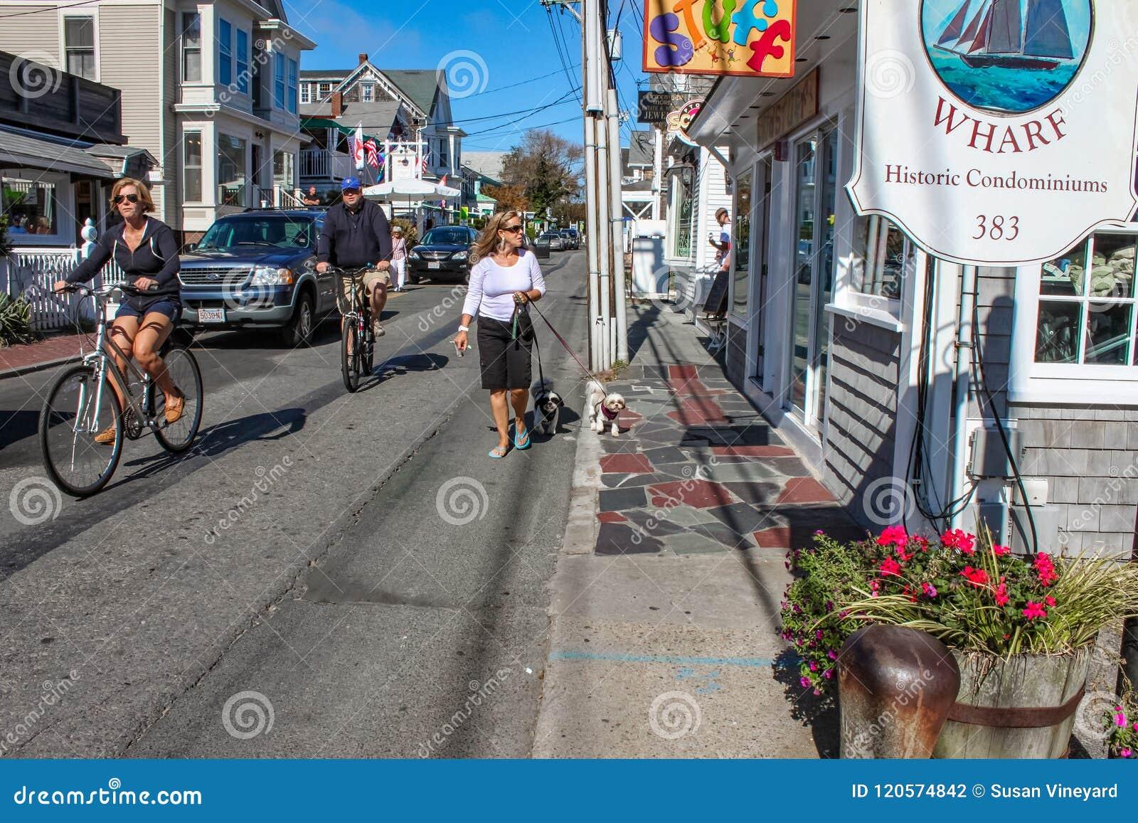 Toeristen die en onderaan hoofdstraat het onderzoeken lopen die de bicycling winkelt met auto s langs de straat en de leuke honde