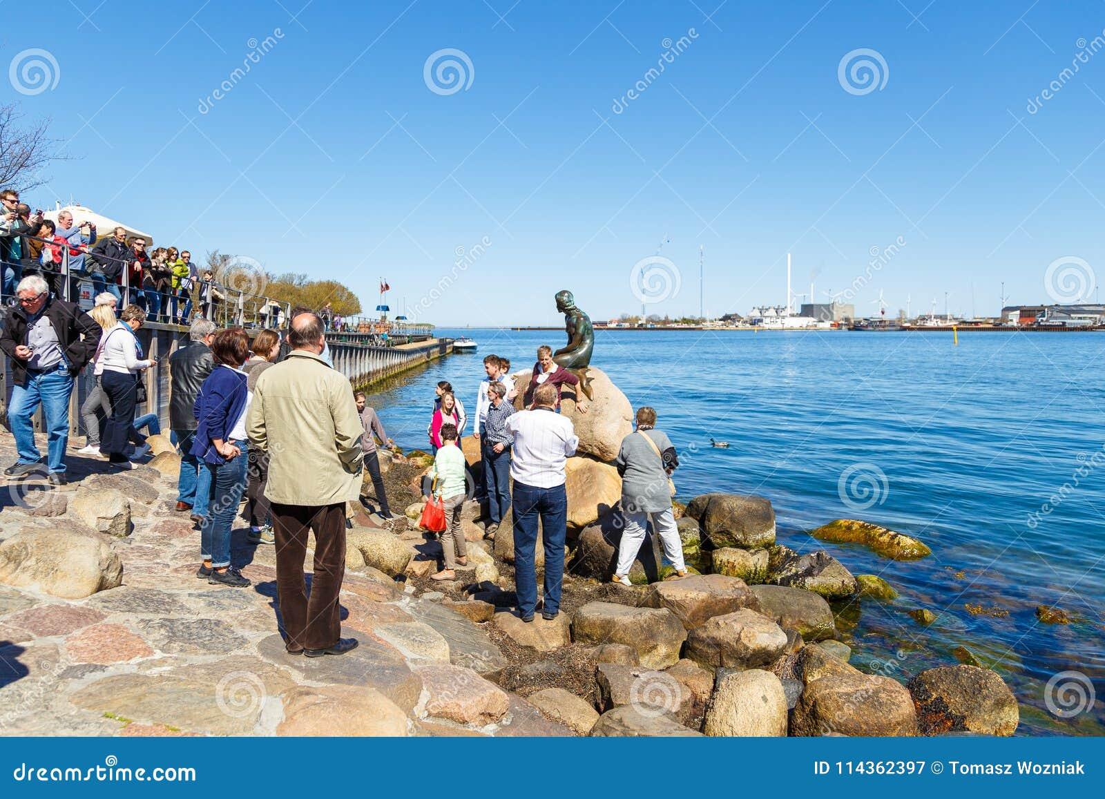 Toeristen die op het Kleine standbeeld van het Meerminbrons afschilderend letten een meermin