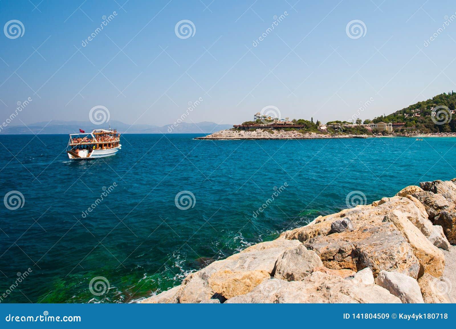 Toeristen op een boot, jacht, schip dichtbij de kust worden gevaren die