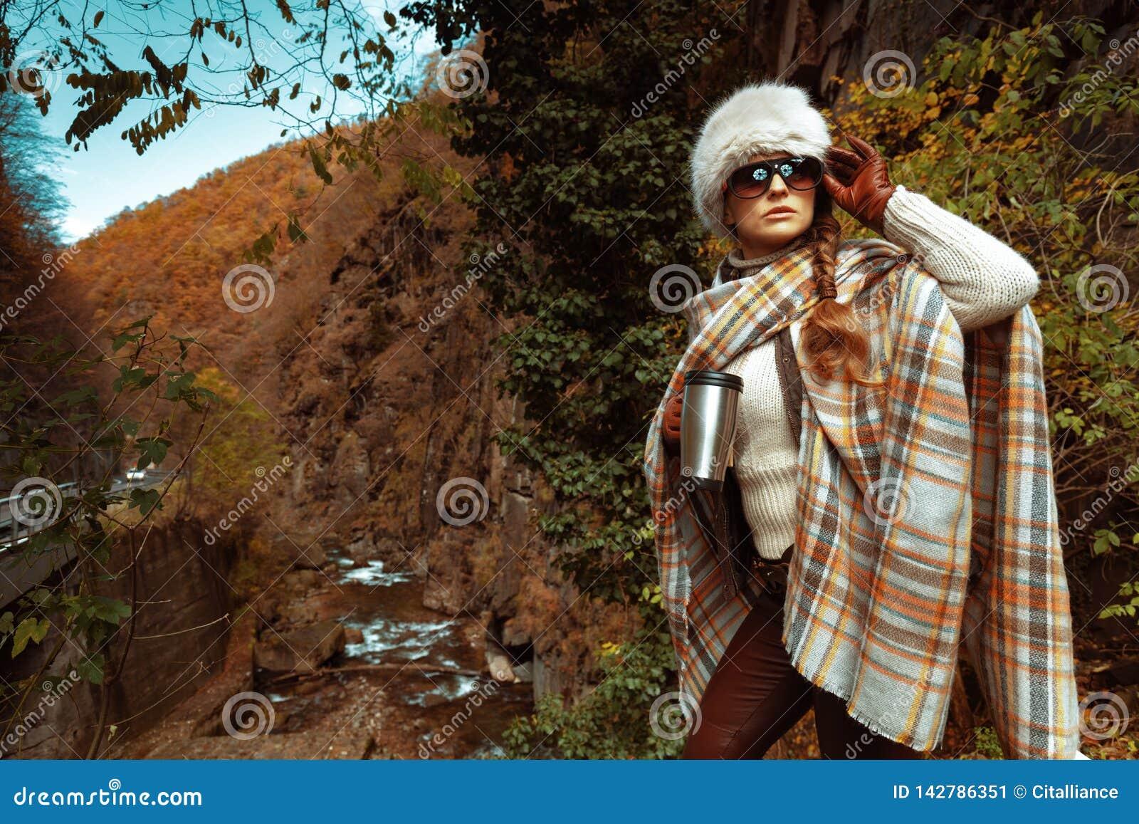 Toeristenvrouw die met de mok van reisthermosflessen de afstand onderzoeken